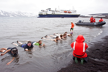 Guests from the Lindblad Expedition ship National Geographic Explorer lay in the relatively warm waters of the caldera at Deception Island, South Shetland Islands, Antarctica