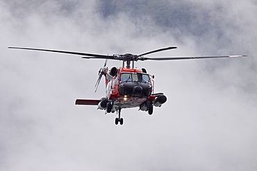 U.S. Coast Guard helicopter performing a rescue operation in Southeast Alaska, USA, Pacific Ocean.