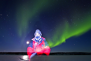 Self-portrait with aurora borealis (Northern (Polar) Lights) over the boreal forest outside Yellowknife, Northwest Territories, Canada