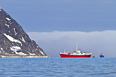 A view of the red expedition ship Antarctic Dream operating in the Svalbard Archipelago, Norway.