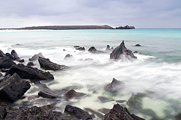 Surf breaking on lava shoreline at Gardner Bay on Espanola Island in the Galapagos Island Archipelago, Ecuador. MORE INFO Slow shutter speeds allow for surreal water movement in this photograph.