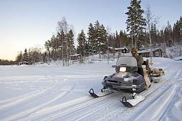 Man on a snowmobile driving over frozen lake, Sweden