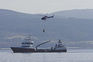 Helicopter supplying salmon farm. Hebrides, UK.