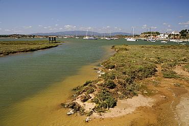 Saltmarsh, estuarine harbour at high tide and moored sailing yachts, Alvor, near Portimao, Algarve, Portugal, Europe