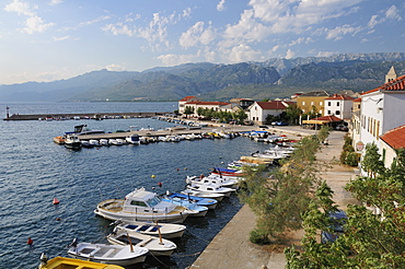 Overview of Vinjerac fishing  village and harbour with the karst limestone Velebit mountain range of the Dinaric Alps in the background, Zadar province, Croatia.