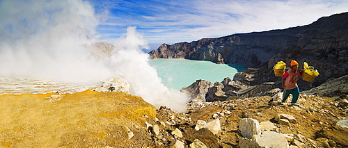 Panorama of sulphur worker appearing out of toxic fumes at Kawah Ijen volcano, East Java, Indonesia, Southeast Asia, Asia