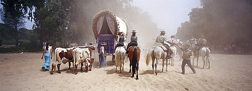 Pilgrims travelling afoot, on horseback and with oxcarts on the sandy Raya Real, Andalusia, Spain