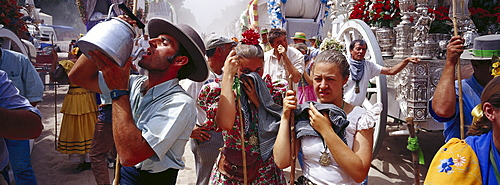 Pilgrims suffering from the heat and dust on the sandy Raya Real, Andalusia, Spain