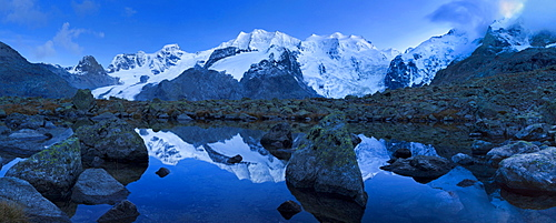 View from a pristine mountain lake at the end of the Morteratsch valley to the summits of Cambrena Piz, Piz Palu, Piz Zupo and Piz Bernina and their reflection, Engadin, Switzerland