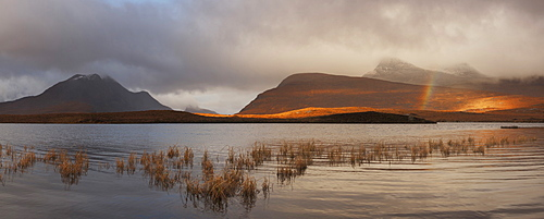 View from Lochan an Ais to the peaks of the Inverpolly Nature Reserve with a rainbow over the lake, Ullapool, Sutherland, Scotland, United Kingdom