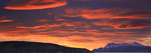 Red lenticular clouds over Teslin Lake and Dawson Peaks at sunrise, Teslin, Yukon