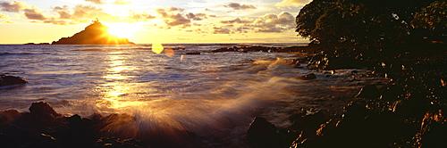 Hawaii, Maui, Hana, View of sunrise bursting over Alau Island from Hana shoreline.