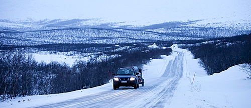 Car with trailer towing a snowmobile travels through arctic wilderness at nightfall by Kilpisjarvi on route from Norway into Finland