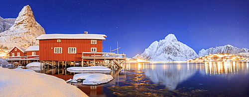 Panoramic view of snowy peaks and the frozen sea on a starry winter night, Reinevagen Bay, Nordland, Lofoten Islands, Arctic, Norway, Scandinavia, Europe