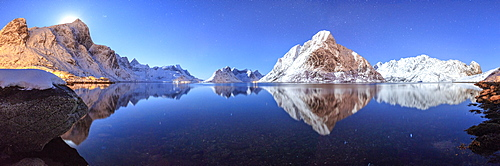 Panoramic view of snowy peaks reflected in the frozen sea on a starry night, Reine Bay, Nordland, Lofoten Islands, Arctic, Norway, Scandinavia, Europe