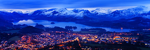 Looking over Keswick to Derwent Water and the snow capped mountains in the Lake District National Park at dusk, Cumbria, England, United Kingdom, Europe
