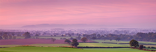 Autumn dawn across the Cheshire plain with Beeston Castle and the Peckforton Hills receding into the morning mist, Cheshire, England, United Kingdom, Europe