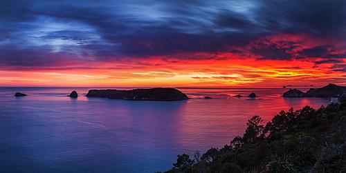 A fiery dawn sky breaks beyond the islands off the Coromandel Peninsula, Waikato, North Island, New Zealand, Pacific