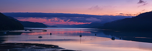 Panorama of Queen Charlotte Sound at dawn with the pink sky and anchored boats reflected in the still water around Okiwa Bay, Marlborough, South Island, New Zealand, Pacific