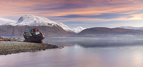 Beached fishing boat and view to a snow capped Ben Nevis from Loch Linnhe, Corpach, Highlands, Scotland, United Kingdom, Europe