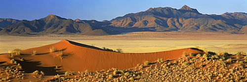 Panoramic view over orange sand dunes towards mountains, Namib Rand private game reserve, Namibia, Africa