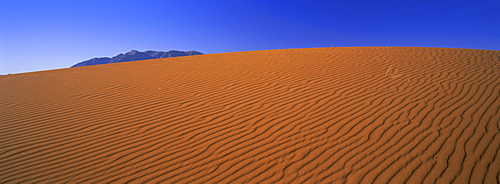 Panoramic view of orange sand dune and blue sky, Namib Rand, a 500000 acre private game reserve in the Namib Naukluft Park, Namibia, Africa