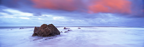 Widemouth Bay at sunrise, with offshore rocks and red storm clouds overhead, near Bude, Cornwall, England, United Kingdom, Europe