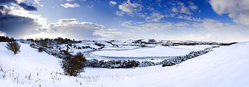 Panoramic view of snow-covered landscape beneath blue winter sky looking towards meandering River Aln, Lesbury, near Alnwick, Northumberland, England, United Kingdom, Europe