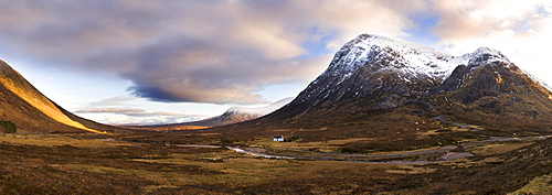 Winter panoramic view of Rannoch Moor showing lone whitewashed cottage on the bank of a river, dwarfed by snow-covered mountains, Rannoch Moor, near Fort William, Highland, Scotland, United Kingdom, Europe