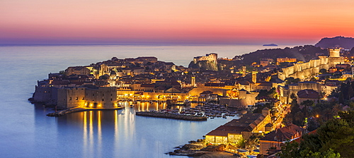 Aerial panorama of Dubrovnik Old Town at night with orange sunset sky, UNESCO World Heritage Site, Dubrovnik, Dalmatian Coast, Croatia, Europe