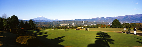 Group of people playing in a golf course with mountains in the background, Mt Fuji, Japan