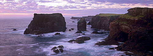 Sunset at Eshaness basalt cliffs, with Moo Stack on left, and deeply eroded coast with caves, blowholes and stacks, Northmavine, Shetland Islands, Scotland, United Kingdom, Europe