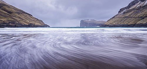 Waves crash against the black sandy beach at Tjornuvik on the island of Streymoy, Faroe Islands, Denmark, Europe