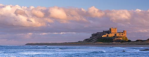 Late evening sunlight bathes the Bamburgh Castle stronghold on the Northumberland coast, Northumberland, England, United Kingdom, Europe