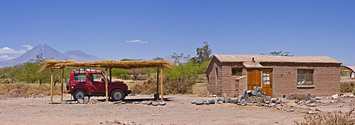 Four-wheel drive vehicle parked under sun shade in front of a small clay house, Licancabur Volcano in background, San Pedro de Atacama, Chile, South America