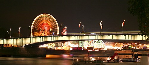 Panorama across Deutzer bridge over the Rhine river and fair lights with the big wheel in Cologne, NRW, Germany