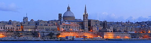 The skyline of Valletta dominated by the floodlit cupola of the Carmelite Church and the tower of St. Paul's Cathedral at the blue hour just after sunset, as seen from Sliema, Malta, Europe
