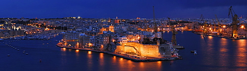 The floodlit Fort St. Angelo on the tip of the peninsula Vittoriosa, Birgu, as seen from Valletta across the Grand Harbor at the blue hour after sunset, Malta, Europe