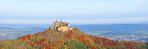 Burg Hohenzollern Castle in the early morning light and fog, with autumnal forest, Swabian Alb, Baden-Wuerttemberg, Germany, Europe