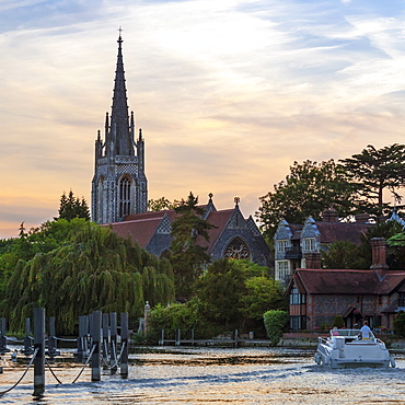 Man and woman on boat with All Saints Church in the background, Marlow, Buckinghamshire, England, United Kingdom, Europe