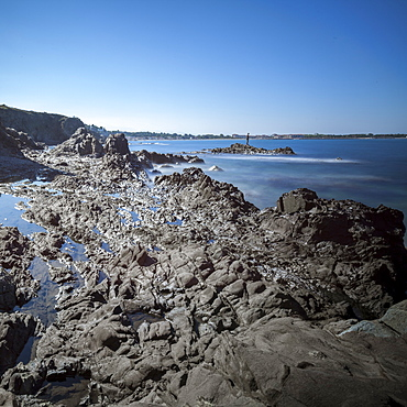 Rocky beach at low tide with man fishing on rock, Argelles, France, Europe