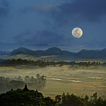 Full moon in Burma, view above hill and pagoda in the morning mist at Mrauk U, Myohaung north of Sittwe, Akyab, Rakhaing State, Arakan, Myanmar, Burma