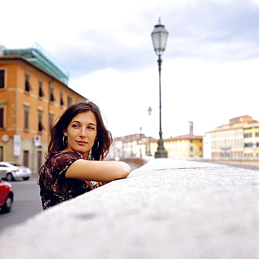 Young woman leaning against wall, Pisa, Italy