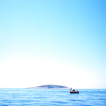 Small fishing boat on Adriatic Sea, island in background, Dalmatia, Croatia