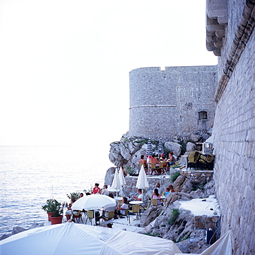 Tourists sitting in the buza bar at city wall, Dubrovnik, Dalmatia, Croatia
