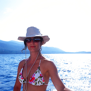 Woman wearing bikini, sunglasses and a hat on a sailboat, Dalmatia, Croatia