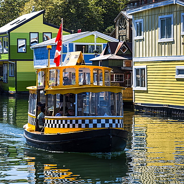 A small tour boat in Fisherman's Wharf in the Inner Harbour of Victoria, Vancouver Island, Victoria, British Columbia, Canada