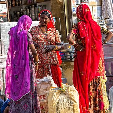 Three Indian women talking outside a shop, Jaisalmer, Rajasthan, India