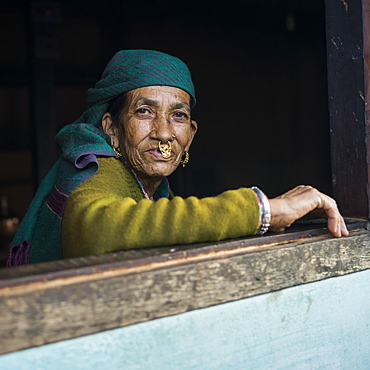 Portrait of an Indian woman looking out a window, Radhu Khandu Village, Sikkim, India
