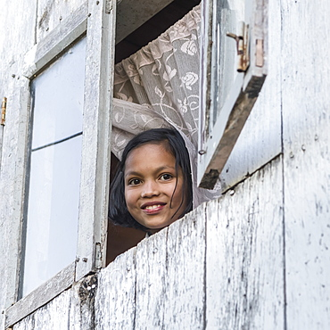 A girl looks out an open window and smiles as she looks down at the camera, Sikkim, India